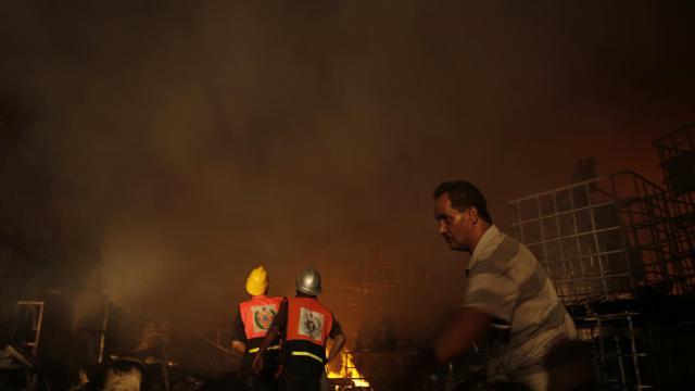 Des pompiers tentent d'éteindre un incendie d'une usine de savon à la suite d'un bombardement israélien, le 10 août 2014 sur la bande Gaza [Mohammed Abed / AFP]