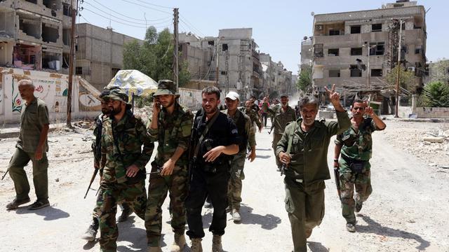 Les forces gouvernementales syriennes font le signe de la victoire à Mleiha dans la banlieue de Damas le 15 août 2014 [Louai Beshara / AFP]