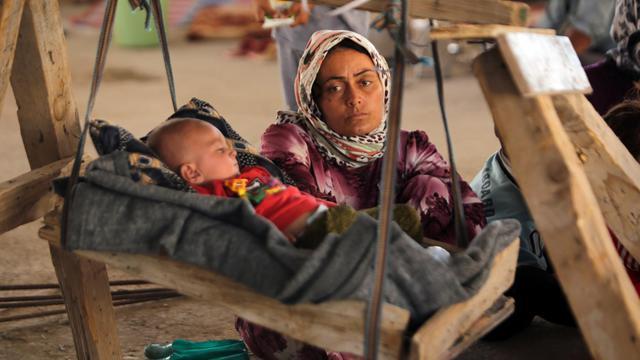 Une femme irakienne yazidi, qui a fui sa maison attaquée par des combattants de l'EI, regarde son bébé dans un immeuble en construction de la banlieue de Dohouk où ils ont trouvé refuge, le 16 août 2014 [Ahmad al-Rubaye / AFP]