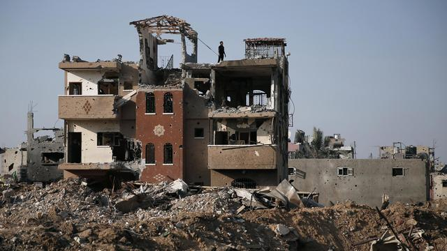 Un Palestinien sur le toit d'un immeuble détruit dans le quartier de Shejaiya, à Gaza, le 17 août 2014 [Thomas Coex / AFP]
