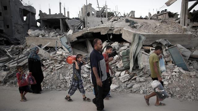 Des familles palestiniennes quittent leurs maisons détruites pour s'abriter dans un bâtiment de l'Onu le 18 juin 2014 à Hanoun dans la Bande de Gaza [Thomas Coex / AFP]