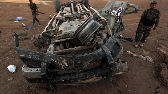 Des peshmergas inspectent l'épave d'un véhicule aux couleurs de l'Etat islamique, détruit par une frappe américaine, à Baqufa au nord de Mossoul, le 18 août 2014 en Iraq [Ahmad Al-Rubaye / AFP]