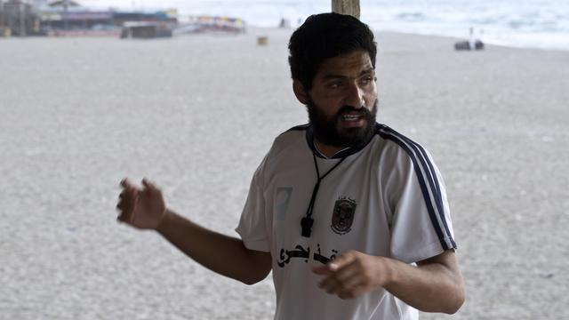 Mohammed Bar, sifflet et palmes à portée de main, est resté fidèle à son poste en surveillant la plage de Gaza pendant les frappes israéliennes  [Roberto Schmidt / AFP]