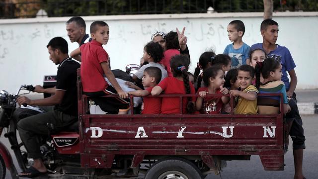 Des Gazaouis fuient le quartier périphérique de Chajaya et se dirigent vers une école de l'ONU, le 19 août 2014 [Thomas Coex / AFP/Archives]