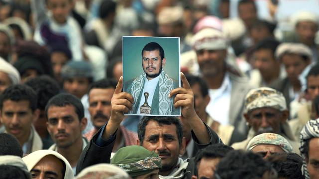 Un chiite brandit la photographie du chef rebelle d'Ansaruallah, Abdel Malek al-Houthi, qui a ordonné à ses partisans de marcher sur Sanaa pour renverser le gouvernement le 20 août 2014 à Hamdan, à 10 km de l'aéroport international de Sanaa [Mohammed Huwais / AFP]