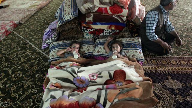 Des petites filles boivent leur biberon dans la mosquée de Hajyawa, le 21 août 2014. De nombreuses familles kurdes de Turquie, déjà exilées dans le nord de l'Irak depuis les années 1990, ont trouvé là refuge après avoir fui devant l'avancée des troupes de l'Etat islamique [Ahmad al-Rubaye / AFP]