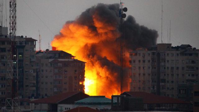 De la fumée au dessus d'un immeuble touché par une frappe israélienne le 23 août 2014 à Gaza [Mohammed Othman / AFP]