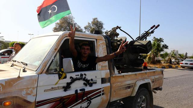Un combattant islamiste de Fajr Libya fait le signe de la victoire à l'entrée de l'aéroport de Tripoli le 24 août 2014 [Mahmud Turkia / AFP/Archives]