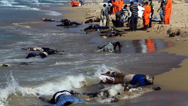 Des secouristes sur la plage d'al-Qarbole, où gisent des corps de migrants clandestins à 60 km à l'est de Tripoli, en Libye le 25 août 2014  [Mahmud Turkia / AFP]