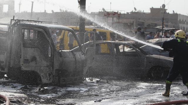 Un membre des services d'urgence éteint les fumées après un attentat à la voiture piégée le 26 août 2014 à Bagdad (Irak) [Amer al-Saedi / AFP]