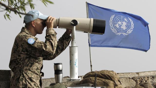 Un membre européen de la Force de l'ONU chargée de l'observation du désengagement (Undof), contrôle la frontière syrienne à partir du Golan en Israël, le 30 août 2014 [Ahmad Gharabli / AFP]