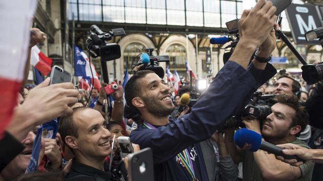 Mahiédine Mekhissi se photographie avec des fans, le 18 août 2014 à la gare de Lyon à Paris [Fred Dufour / AFP]