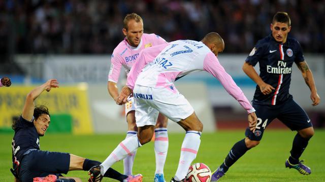 L'attaquant uruguayen du Paris SG Edinson Cavani tacle le défenseur français d'Evian-Thonon-Gaillard Aldo Angoula lors d'un match de L1 entre les deux équipes, le 22 août 2014 à Annecy. [Jean-Pierre Clatot / AFP]