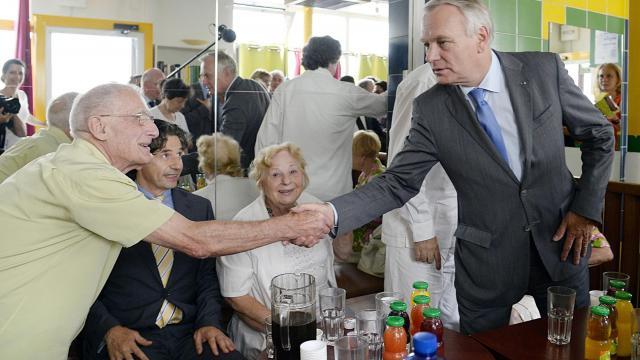 Le Premier ministre Jean-Marc Ayrault (d) rencontre le 2 août 2013 des personnes âgées à Paris [Bertrand Guay / AFP]