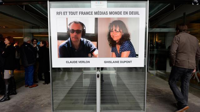 Les portraits de Ghislaine Dupont et Claude Verlon, affichés le 5 novembre 2013 à l'entrée du siège de RFI [Bertrand Guay / AFP]