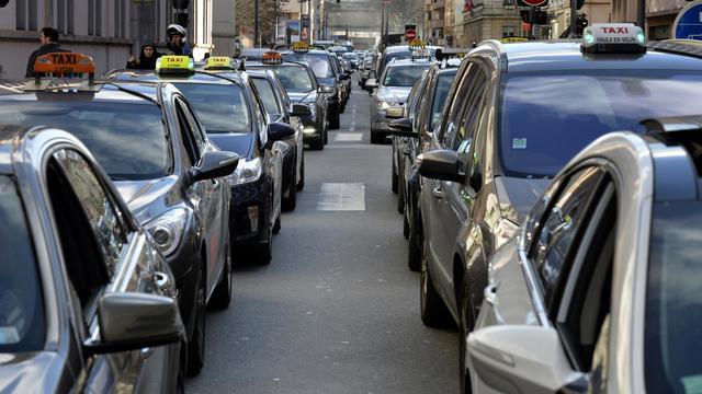 Des chauffeurs de taxis en grève bloquent la circulation à Lyon, le 12 février 2014 [Jean-Philippe Ksiazek / AFP]