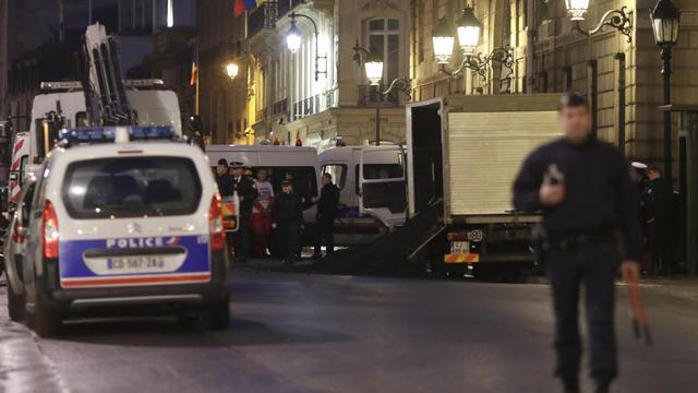 Un policier se tient devant un camion de Greenpeace ayant déversé cinq tonnes de charbon aux portes de l'Elysée, à Paris, le 19 février 2014 [Kenzo Tribouillard / AFP]