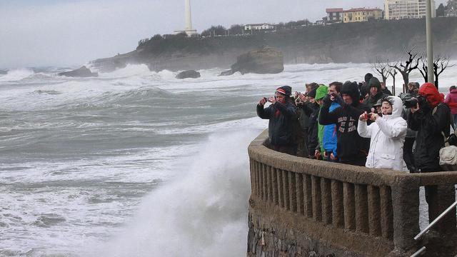 Le rivage balayé par de hautes vagues le 3 mars à Biarritz où des passants prennent de photos [Daniel Velez / AFP]