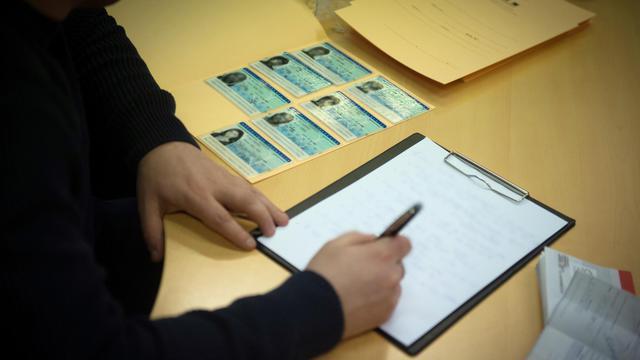 Un policier de l'Office central pour la répression de l'immigration irrégulière et de l'emploi d'étrangers sans titres (Ocriest) rédige un rapport sur un trafic de pièces d'état civil à Lognes le 3 mars 2014 [Martin Bureau / AFP]