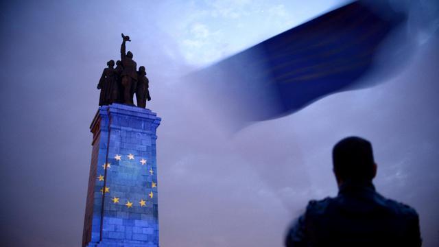 Symbole du tiraillement de la Bulgarie, à Sofia, le 8 mai 2014, un homme agite un drapeau européen devant le monument dédié à l'armée soviétique, illuminé par les étoiles jaunes sur fond bleu, symbolisant.. l'Europe [Nikolay Doychinov / AFP]