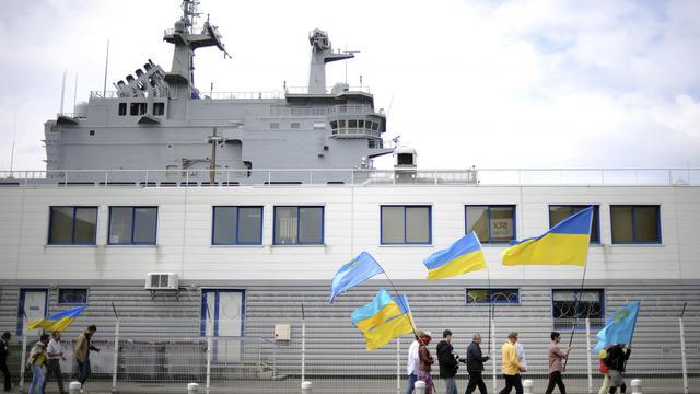 Des personnes manifestent avec des drapeaux ukrainiens devant un navire de guerre vendu à la Russie, à Saint-Nazaire le 1er juin 2014  [Jean-Sebastien Evrard / AFP/Archives]