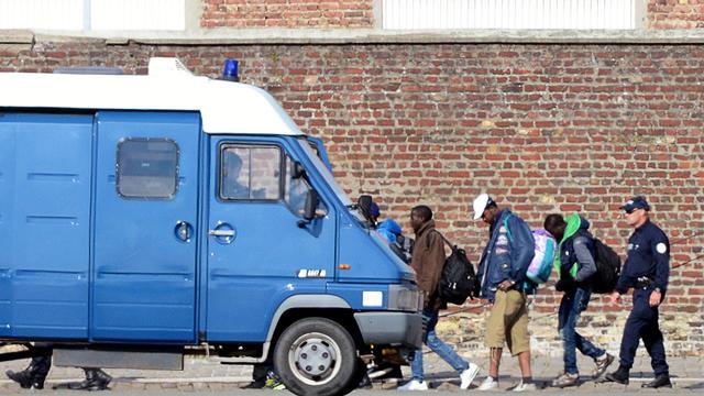 Des policiers français conduisent des clandestins expulsés de leur camp à Calais pour les amener dans un centre de rétention, le 2 juillet 2014 [Denis Charlet / AFP]