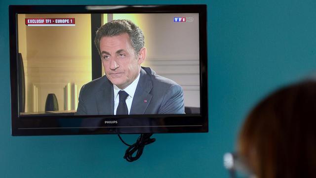 Une femme regarde Nicolas Sarkozy sur TF1, le 2 juillet 2014 [Denis Charlet / AFP/Archives]