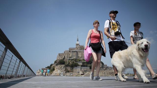 Des touristes sur le pont-passerelle menant au Mont-Saint-Michel (Manche), le 22 juillet 2014 [Charly Triballeau / AFP]