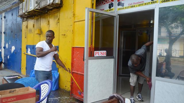 Des hommes nettoient leurs bureaux à Monrovia contre l'épidémie d'Ebola le 1er août 2014 [Zoom Dosso / AFP]