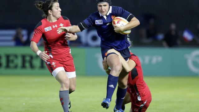 La Française Shannon Izar tente d'échapper au plaquage de deux joueuses galloises lors d'une rencontre comptant pour la Coupe du Monde de rugby féminin, le 1er août 2014 à Marcoussis, dans l'Essonne. [Kenzo Tribouillard / AFP/Archives]