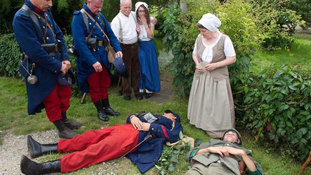 Des acteurs jouent le lieutenant allemand Mayer (droite) et le caporal français Peugeot (au centre), gisant au sol, lors d'un hommage à Joncherey le 2 août 2014 [Sébastien Bozon / AFP]