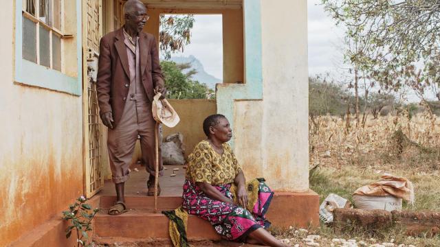 Mwamkono Mwavaka, dont le grand-père fut enrôlé de force comme porteur dans l'armée britannique pendant la Première Guerre mondiale, se tient sur le perron de sa maison avec sa femme, le 26 juillet 2014, à Taita Taveta, dans le parc national de Tsavo [Nichole Sobecki / AFP]