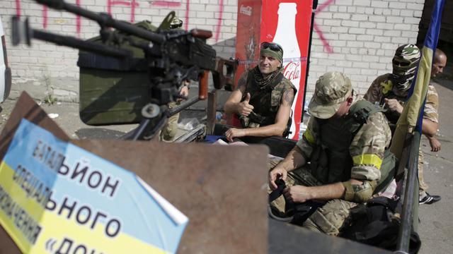 """Des soldats ukrainiens du bataillon de volontaires """"Donbass"""" se préparent à un redéploiement à partir de Popsana, une localité de la région de Lougansk prise aux séparatistes prorusses, le 4 août 2014 [Anatolii Stepanov / AFP]"""