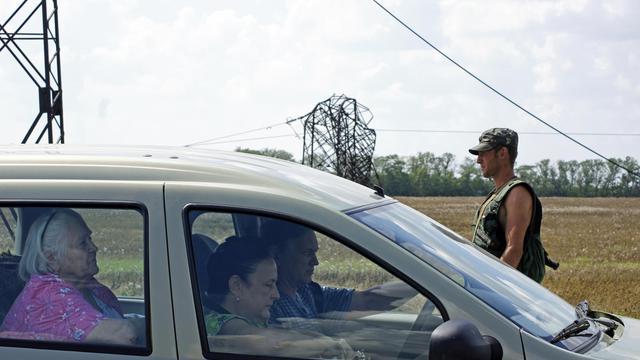 Des passagers sont contrôlés par des forces de l'ordre ukrainiennes, sur la route quittant Donetsk vers Maryinka, le 5 août 2014 [Andrey Krasnoschekov / AFP]