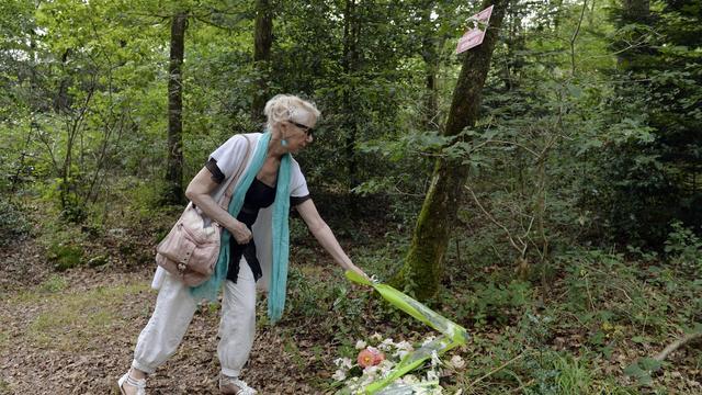 Lucette Rosty dépose des fleurs le 6 août 2014 dans un bois entre Iffendic et Monterfil où trois femmes, Marie, sa tante, Germaine Guillard et Suzanne Lesourd ont été enterrées après avoir été tondues, humiliées et pendues les 3 et 4 août 1944 [Miguel Medina / AFP]