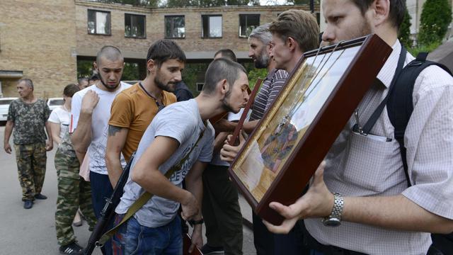 Des militants prorusses embrassent des images sacrées à Donetsk, le 8 août 2014 [Alexander Khudoteply / AFP]