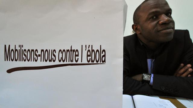 Coulibaly Daouda, chef du secteur épidémiologie au département de la santé d'Abidjan pose à coté d'une pancarte appelant à la mobilisation contre Ebola, le 8 août 2014 [Issouf Sanogo / AFP]