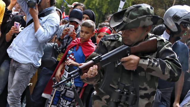 A Paris, samedi 9 aout 2014, un manifestant propalestinien pointe une kalachnikov qu'il affirme être factice et se livre à un simulacre d'exécution d'enfants. Une enquête préliminaire pour port d'armes a été ouverte dimanche [Kenzo Tribouillard / AFP]