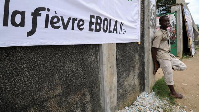 """Un homme accoté à un mur près d'une banderole sur laquelle on peut lire: """"La fièvre Ebola!!"""", le 10 août 2014 à Abidjan  [Sia Kambou / AFP]"""