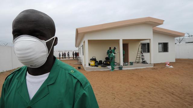 Un homme portant un masque de protection devant un centre de quarantaine pour les personnes atteintes du virus Ebola à l'aéroport d'Abidjan, le 12 août 2014 [Sia Kambou / AFP]