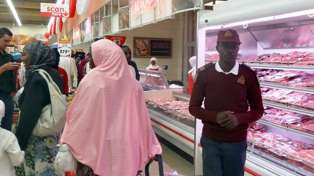 A droite, un garde de sécurité dans un centre commercial à Kano au nord du Nigeria, à gauche, une cliente, le 12 aout 2014 [Aminu Abubakar / AFP]