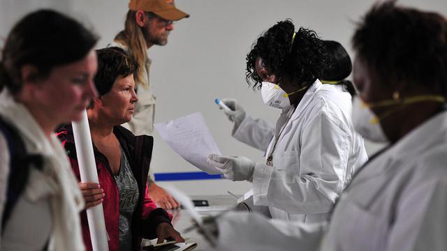 Du personnel médical aide les voyageurs à remplir des formulaires médicaux avant un dépistage du virus Ebola à leur arrivée à l'aéroport international Kenyatta à Nairobi le 14 août 2014 [Simon Maina / AFP/Archives]