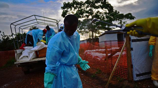 Un membre des services publics de fossoyeurs en Sierra Leone est aspergé de désinfectant tandis que des collègues chargent un camion des corps de victimes du virus Ebola, à Kailahun, le 14 août 2014 [Carl de Souza / AFP]