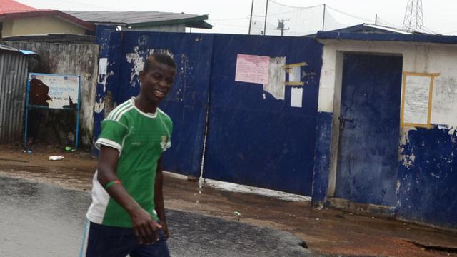 Des passants marchent devant une école transformée en centre d'isolement pour les malades d'Ebola d'où se sont enfuis 17 malades à la suite d'une attaque, le 17 août 2014 à Monrovia au Liberia [Zoom Dosso / AFP]