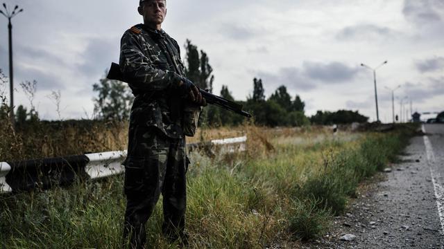 Un rebelle pro-russe le 18 août 2014 sur une route près de Donetsk [Dimitar Dilkoff / AFP]