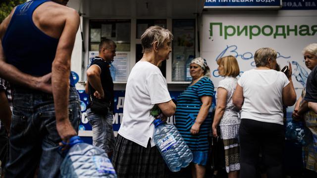 Bonbonnes de plastiques vides à la main, les habitants de Donetsk, patientent dans de longues files d'attente devant des kiosques qui vendent de l'eau minérale au litre, le 18 aout 2014 [Dimitar Dilkoff / AFP]