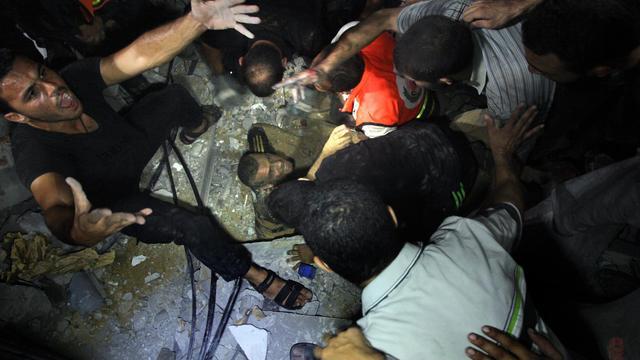 Des secouristes tentent d'extraire des décombres de sa maison un Palestinien blessé le 19 août 2014 à Gaza [Ezz Al-Zanoun / AFP]