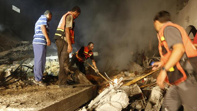 Des Palestiniens dans les ruines d'une maison détruite par un tir israélien le 19 août 2014 à Gasa [Mohammed Abed / AFP]