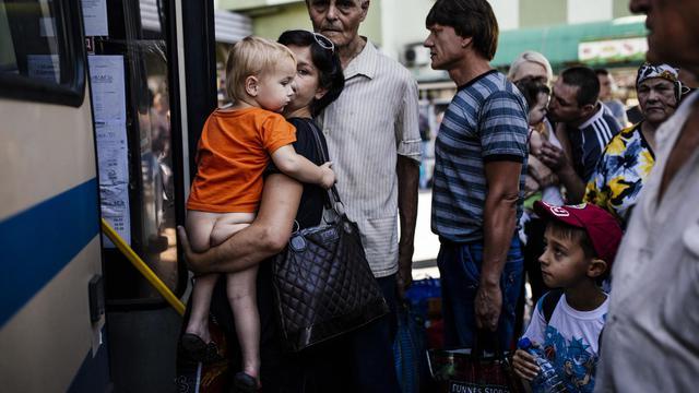 Une mère et son enfant monte dans un autobus à Donetsk où les combats s'intensifient, le 20 août 2014 [Dimitar Dilkoff / AFP]