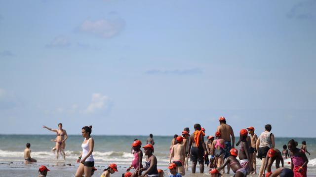 Des enfants venus d'Ile de France avec le Secours populaire jouent sur une plage d'Ouistreham (Calvados) le 20 août 2014 [Charly Triballeau / AFP]